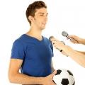 Homme avec ballon de foot dans les mains et micro devant lui